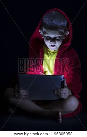 Funny boy sitting with a tablet in the dark before bed time