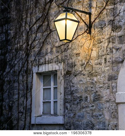 The wall of the house with a window and a lantern in the old city in European country
