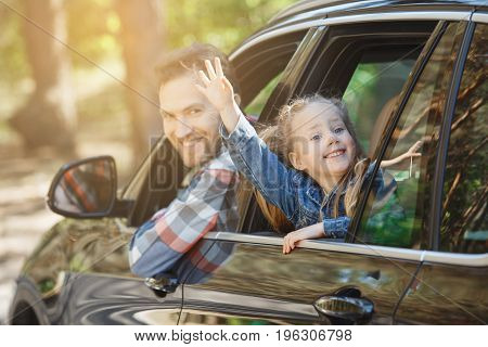 Travel by car family ride together father and daughter lean out of the window