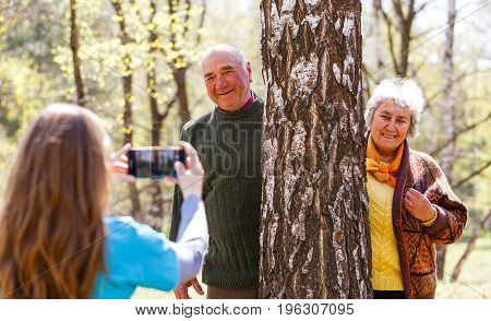 Photo of young caregiver taking photo of elderly couple