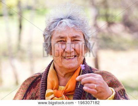 Portrait photo of happy elderly woman holding flower in hand
