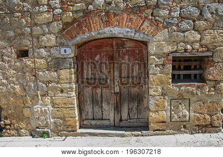 View of wooden door in a stone wall in the hamlet of Monteriggioni. A medieval fortress, surrounded by stone walls, at the top of a hill, near Siena. Located in the Tuscany region