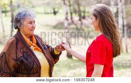 Photo of young carer giving flower for elderly woman
