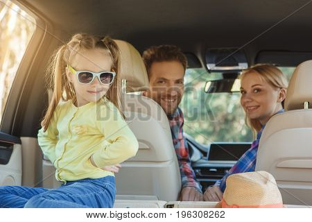 Travel by car family ride together daughter playing with sunglasses