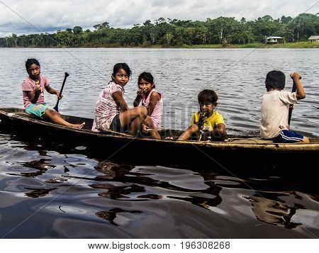 AMAZON RIVER PERU - 16 FEBRUARY 2016 - Unknown children from local rainforest village in their wooden boat try to sell handcraft items to tourists