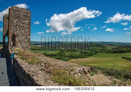 View of fields and hills of Tuscany from above the walls of the Monteriggioni hamlet. A medieval fortress, surrounded by stone walls, at the top of a hill, near Siena. Located in the Tuscany region