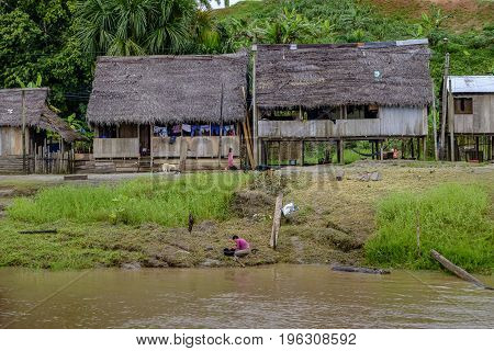 AMAZON RIVER PERU - 16 FEBRUARY 2016 - Woman washing laundry in a plastic basin by the banks of the Amazon River in Peruvian rainforest with background of typical wooden shack housing