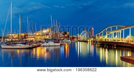 Panorama with Port Vell marina and wavy wooden walkway known as the Rambla de Mar at night in Barcelona, Catalonia, Spain.