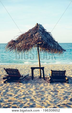 Sunbed And Nipa Umbrella On The Beach During Sunset