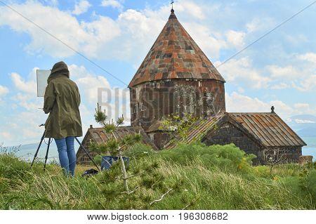 Female painter draws a church in the ancient monastery Sevanavank in Armenia