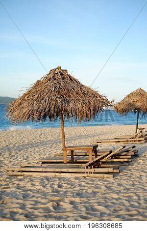 Sunbed And Nipa Sun Umbrella On The Beach During Sunset