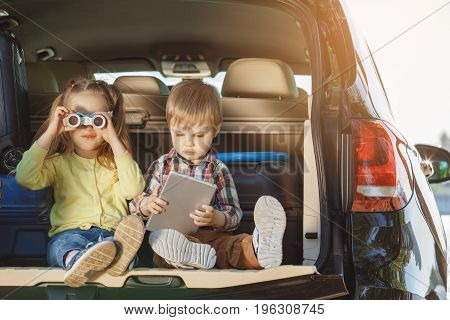 Travel by car, family together, brother and sister sitting the way back.