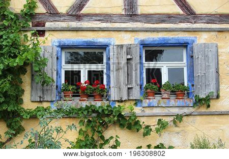 two old windows with shutters and red geraniums in a half-timbered house