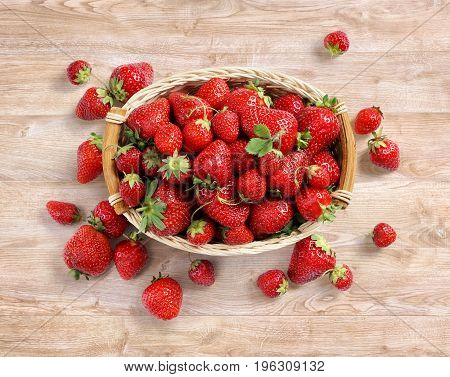 Fresh strawberry in basket on wooden background. Top view. High resolution. Harvest concept