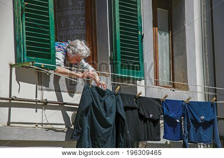 Colle di Val d'Elsa, Italy - May 13, 2013. View of elderly woman putting clothes to dry at window in Colle di Val d'Elsa. A town well preserved and famous for its crystal production. Tuscany region