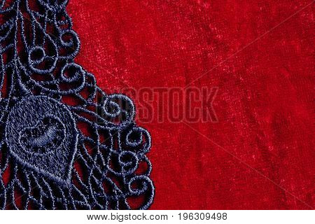 Detail of black lace on red velvet closeup space for text vintage composition