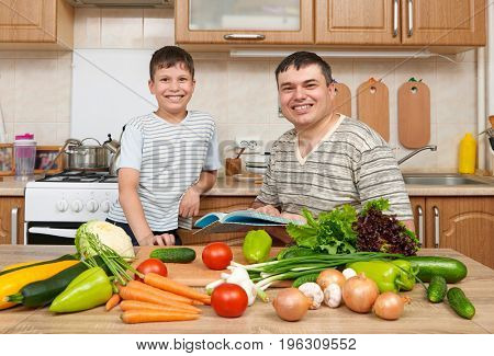 Father and child reading cooking book and choice dishes. Happy family having fun with fruits and vegetables in home kitchen interior. Healthy food concept.