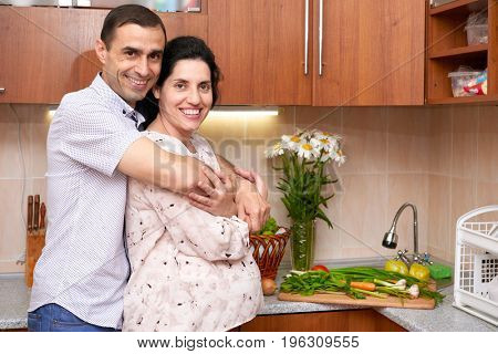couple in kitchen interior with fresh fruits and vegetables, healthy food concept, pregnant woman and man