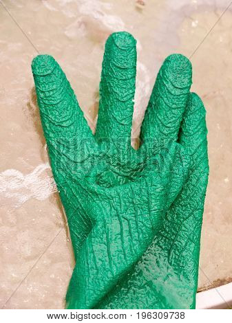 a wet single green gloves on glass table; Essex; UK