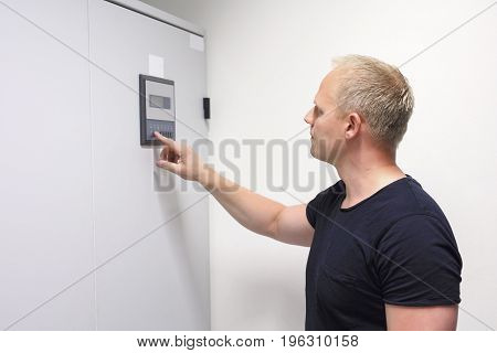 Mid adult male computer engineer pressing button on control panel to adjust air conditioner in datacenter