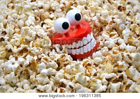 teeth with eyes eat popcorn on a ground of popcorns funny