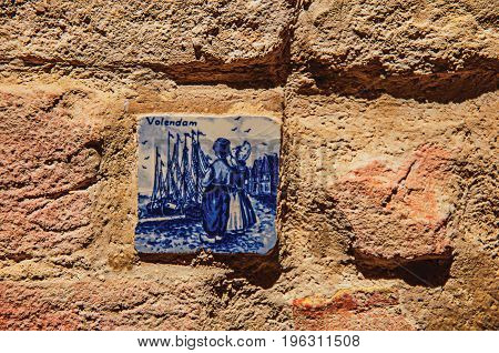 Close-up of ceramic tile attached to the wall in Colle di Val d'Elsa. A graceful village with its historic center preserved and known by its crystal production. Tuscany region. Retouched photo