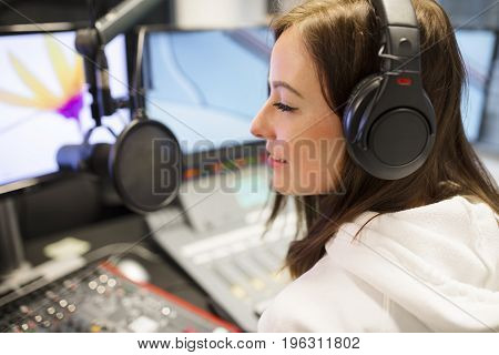 Closeup of young female host wearing headphones at radio studio