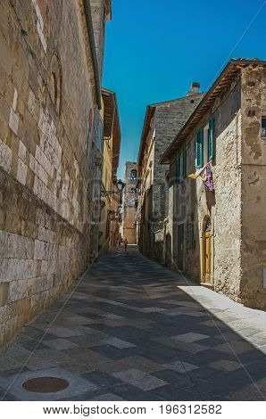 View of narrow alley with old buildings and belfry in Colle di Val d'Elsa. A graceful village with its historic center preserved and known by its crystal production. Located in the Tuscany region