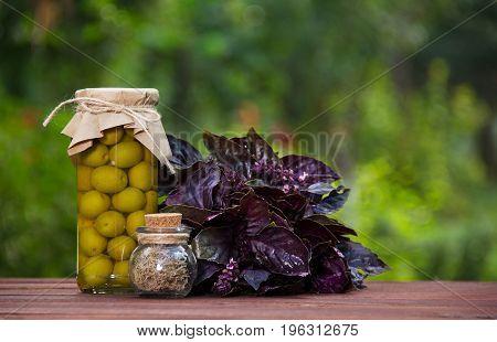 Italian olives in oil and fragrant basil. Green olives in a jar and fragrant herbs on a table.