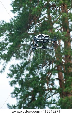 Quadrocopter with digital camera flies in forest against background of trees