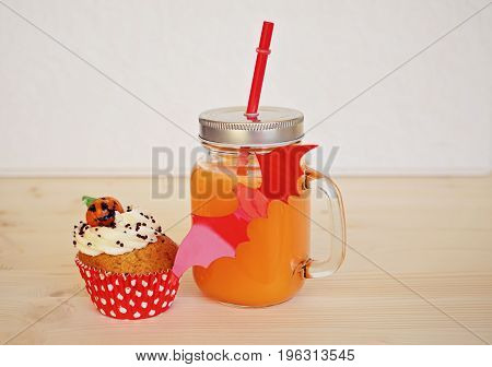 Big jar with orange juice and cupcake for halloween party and red bat