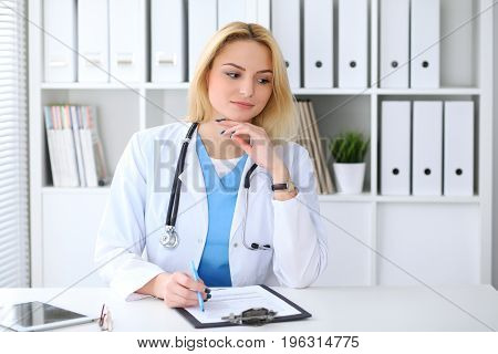 Doctor woman filling up medical form while  sitting at the desk. Medicine and health care concept.