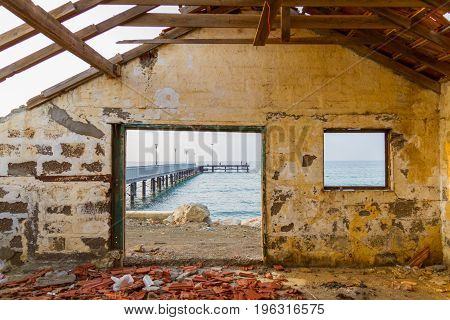 Pier View Through Derelict House Window By The Beach