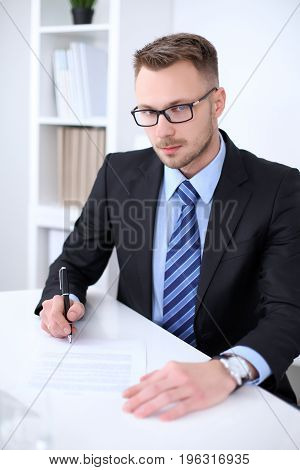 Portrait of businessman sitting at the desk in office workplace.