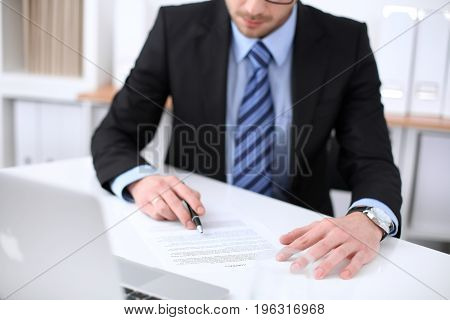 Young business man signs contract while sitting at the desk in office, close up of hands.