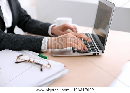Close up of business woman hands typing on laptop computer in the white colored office