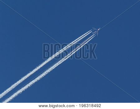 Aircraft and Diagonal Condensation Trails or Contrails on blue sky