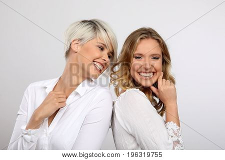 Two beautiful young blonde woman laughing white backgroung