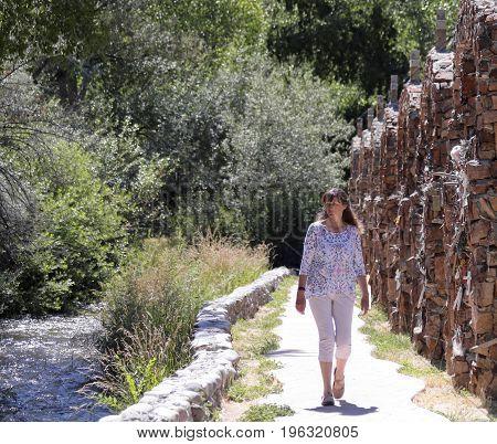 CHIMAYO, NEW MEXICO, JULY 5. El Santuario de Chimayo on July 5, 2017, in Chimayo, New Mexico. A Woman Walks the Grounds of El Santuario de Chimayo in Chimayo New Mexico Built in 1816.