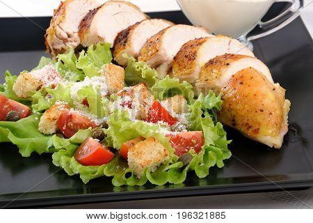 Sliced baked chicken breast with garnish a la Caesar.