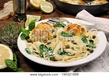 Spaghetti with chicken meatballs in cheese cream sauce spinach and capers