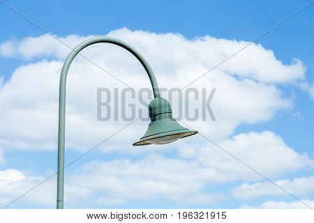 Hanging street lamp on blue sky background with clouds.
