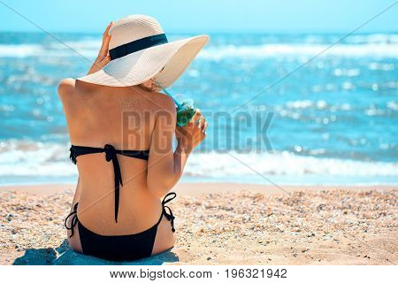Back view of woman in hat and bikini having refreshing drink at seaside.