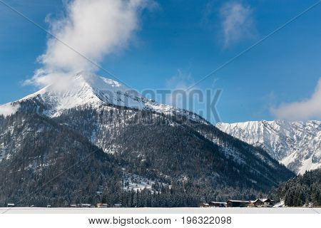 High altitude snow-capped mountains with forested slopes towering above the wooden chalets of a ski resort with white fluffy clouds clinging to the summit
