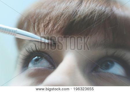 Make Up Vanity 5: self portrait of a woman applying make up to her eyebrow, shallow depth of field bring attention to her brow and bangs