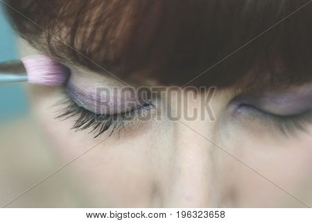 Make Up Vanity 4: self portrait of a woman applying eyeshadow to her right eye lid, a shallow depth of field draws attention to her right eye
