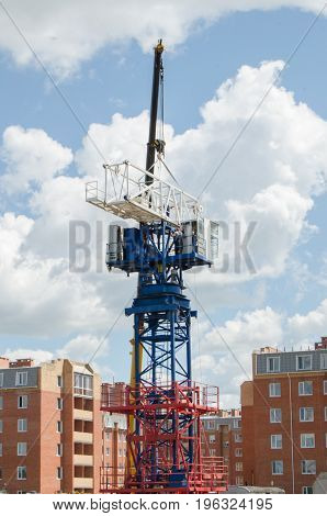 The assembly of the high crane. The crane lift raises part of the boom of the high-rise crane