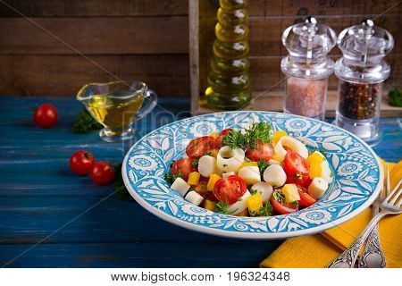 Fresh salad of heart of palm, cherry tomatoes, yellow bell pepper, garlic and parsley on wood blue background. Trendy argentine cuisine with palmitos.
