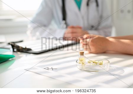 Medicine capsules and pills are lying against the background of a doctor and patient.