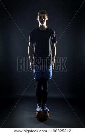 portrait of football player balanced on ball